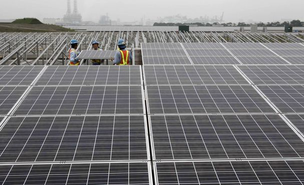 File photo of workers setting up a solar panel at a solar power field in Kawasaki